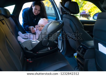 Young mother standing next to her baby sitting in baby seat backwards on backseat of the car with black interior #1232842312