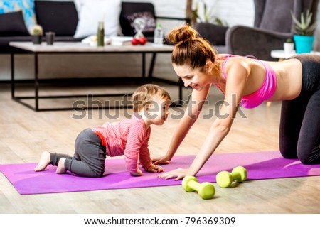 Young mother stretching on the mat with her baby son playing on the floor at home #796369309
