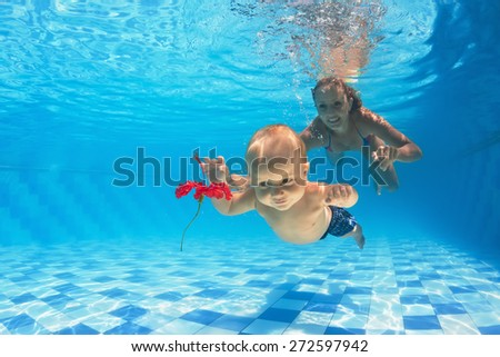 Young mother teaches to swim 10 month old baby - dive with cheerful boy deep into the water for a beautiful red flower, healthy lifestyle and children swimming lessons with an instructor In the pool