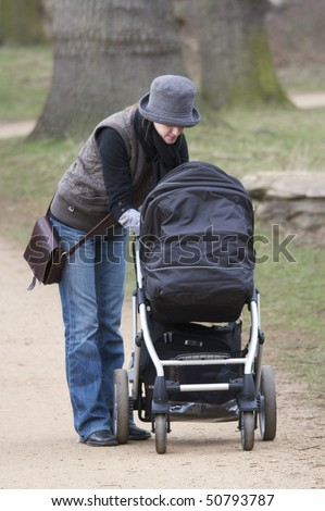 Young Mother tending to her baby in a pushchair while walking in a park