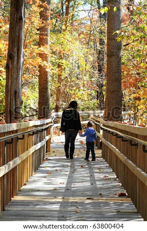 Young mother walking with little girl in a beautiful autumn park.