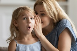 Young mother whisper in surprised cute little daughter ear tell secret, millennial mom or nanny play with small preschooler girl child, share close intimate moment at home, gossip or chat together