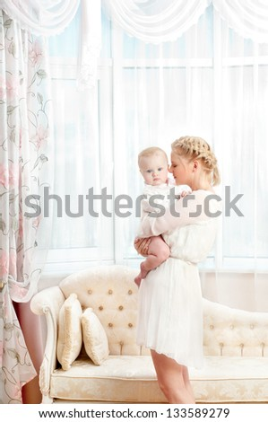 young mother with a baby in a beautiful bedroom - stock photo