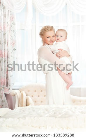 young mother with a baby in a beautiful bedroom