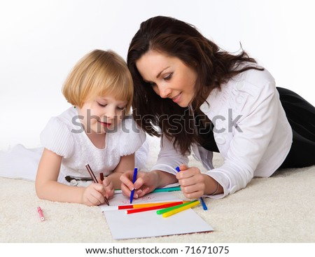 young mother with a daughter on a white carpet drawing with color pencils
