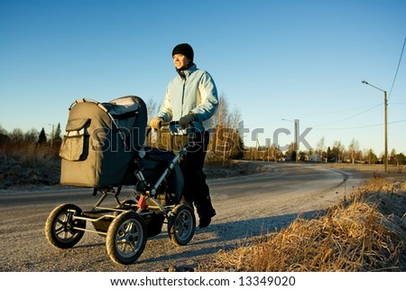 Young mother with a stroller - stock photo