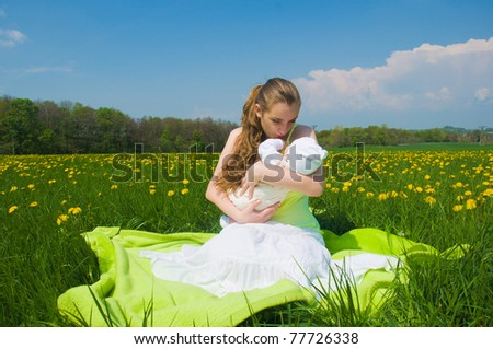 young mother with an infant resting on the meadow