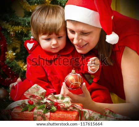 Young mother with  baby  at Christmas tree