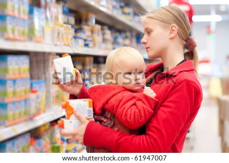 Young mother with baby daughter shopping in supermarket