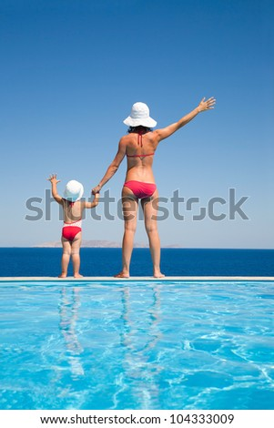 Young mother with baby daughter standing on the edge of the pool and stare at the sea