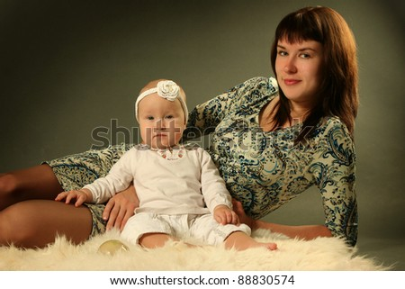 young mother with baby on grey background