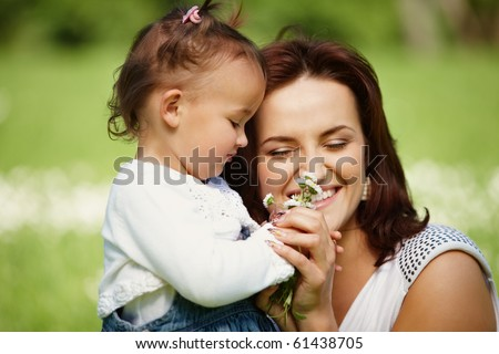 Young mother with child outside on a summer day. Focus is on the girl.