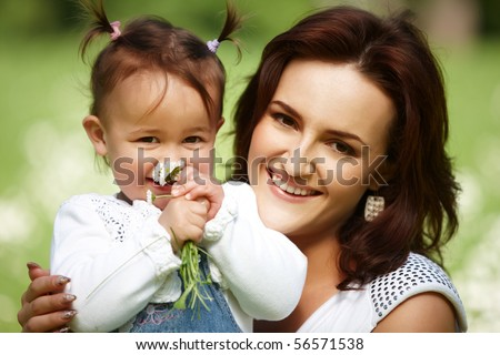 Young mother with child outside on a summer day. Focus is on the woman.