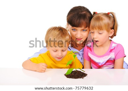 Young mother with children admiring the plant