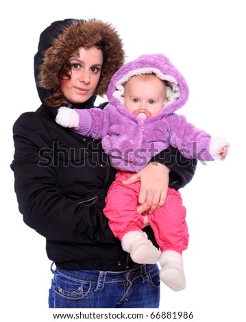 Young mother with cute baby dressed in a fur. Seasonal fashion shot.