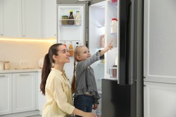 Young mother with daughter near open refrigerator in kitchen