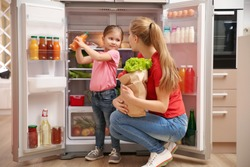 Young mother with daughter putting food into refrigerator at home after shopping