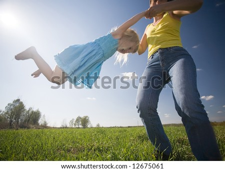 young mother with happy little daughter whirling on green sunny meadow