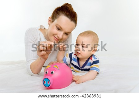 young mother with her adorable newborn baby and a piggy bank