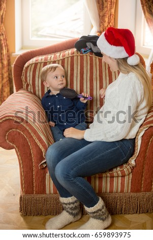 Young mother with her baby sitting on sofa at living room decorated for Christmas #659893975