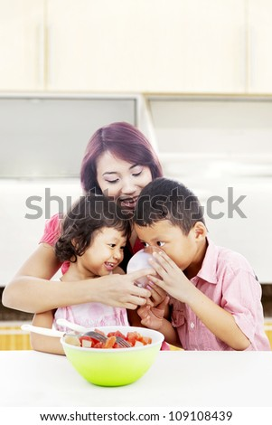 Young mother with her children in the kitchen and helping her son to drink