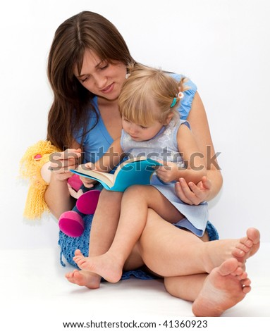 Young mother with her cute daughter reading a book