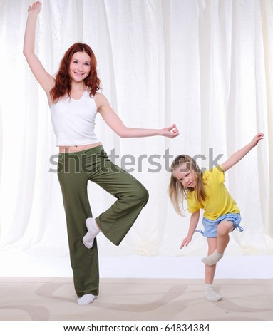 Young mother with her daughter doing sport exercises