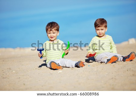 Young mother with her infant kids resting at the beach
