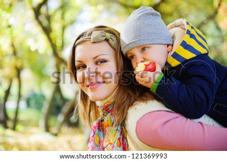 Young mother with her little son eating apple in autumn park