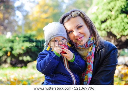 Young mother with her little son eating apple in autumn park - stock photo