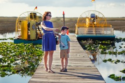 Young mother with her little son on an airboat tour. The Everglades are a natural region of wetlands in the southern portion of the U.S. state of Florida. Boardwalks in the swamp, USA.