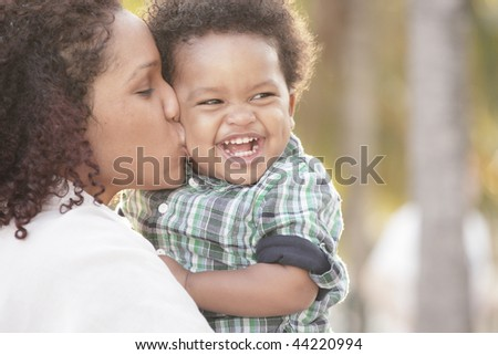Young mother with her smiling toddler in her arms