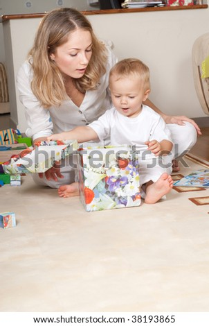 Young mother with her son is opening present box