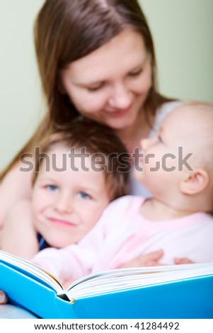 Young mother with her two kids reading book in bed. Focus on book.