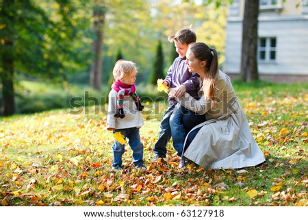 Young mother with here two kids at autumn park