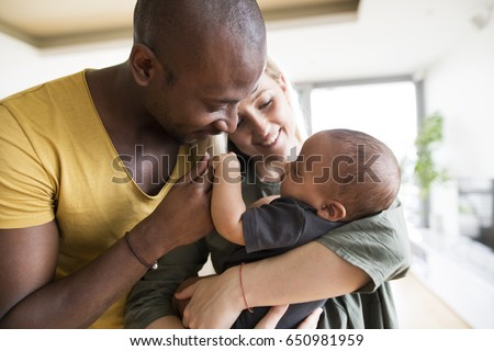 Young mother with his little daughter and her afro-american father at home.