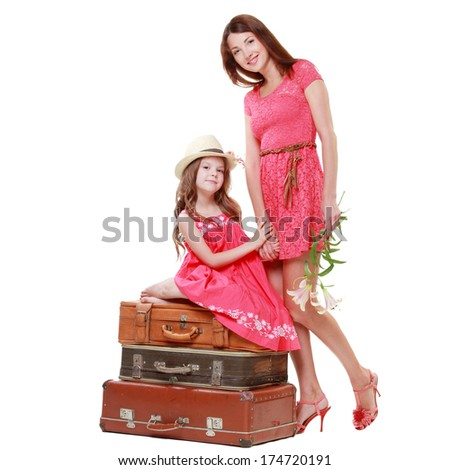 Young mother with his little daughter in a pink dress sitting on suitcases in a travel theme