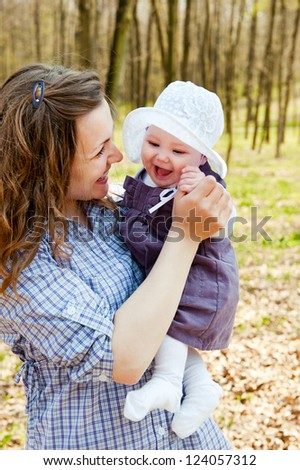 Young mother with little baby daughter in park outdoors