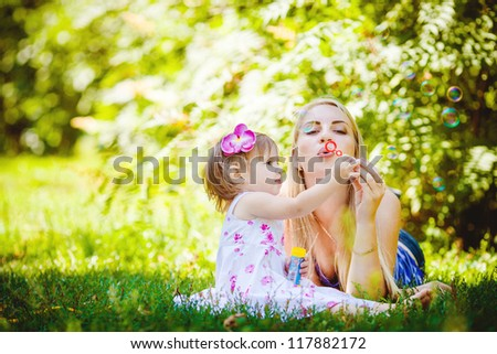 Young mother with little daughter playing in summer park outdoor