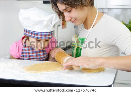Young mother with little daughter rolling dough for cookies
