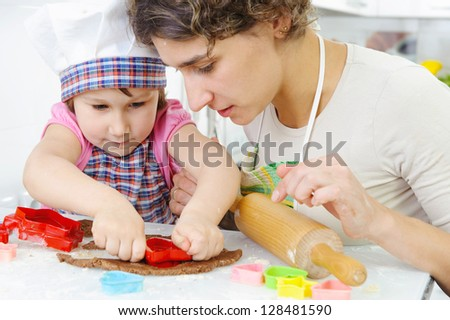 Young mother with little daughter shaping cookies