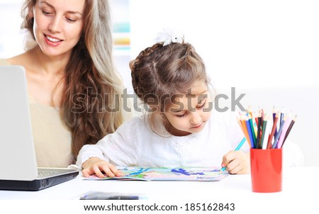 Young mother with little daughter sitting together at home