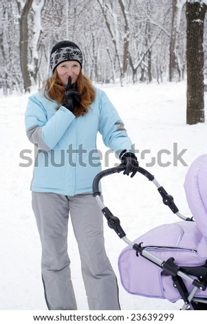 young mother with perambulator on a winter walk asking you to keep quiet
