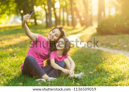 Young mother with pretty daughter make photo in park
