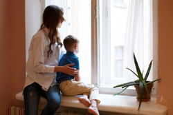 Young mother with son child sitting on window waiting for somebody, looking through window outside, in room or apartment. Missing someone, separation and meet, loneliness and divorce, family