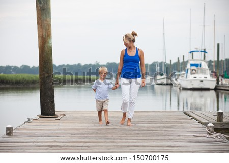 Young mother with son holding hands and walking on dock.