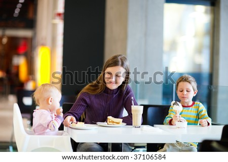 Young mother with two kids enjoying meal sitting at cafe