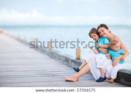 Young mother with two kids on wooden jetty by the ocean