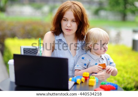 Young mother working oh her laptop and holding her sad toddler son #440534218