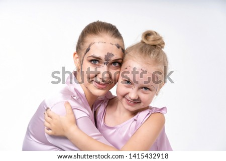 young mothers and young daughter Europeans conduct facial skin care procedures. Family treatments. Cosmetic skin care.
